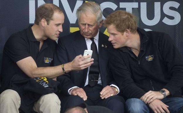 Los príncipes de Inglaterra William (i.) y Harry (d.), con su padre.