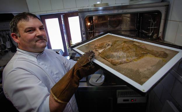 Mikel Bengoa saca un pescado del horno de su local en Meñaka.