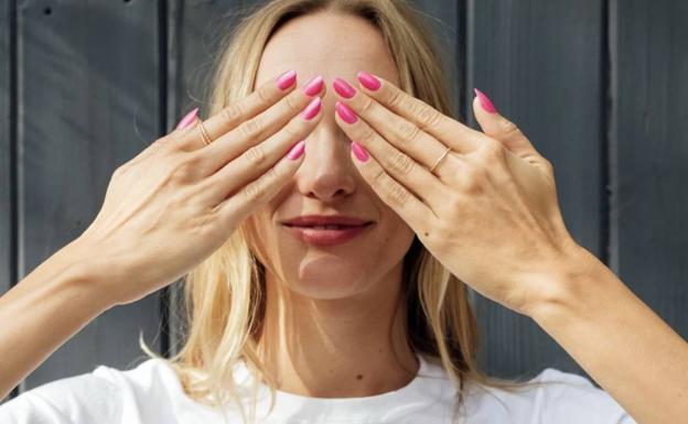 Una mujer muestra su manicura.