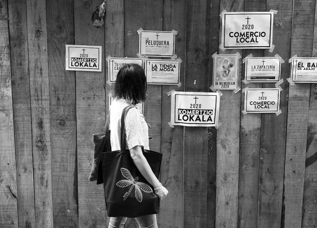 A pedestrian stops in front of the obituaries of the local businesses.